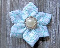 Adorable hair flower tutorial!  Gorgeous quatrefoil printed grosgrain ribbon with a stunning rhinestone/pearl embellishment center! Learn how to make your own ribbon hair flower on the blog with Cassie as she details every step with clear instructions!