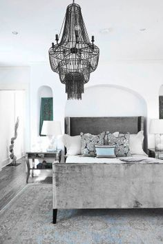 Beautiful transitional master bedroom design with a white, beige, taupe gray, and blue color scheme. The velvet bed, tan and blue patterned carpet and the rusted chain chandelier have a lot of impact in this stylish room - Unique Bedroom Ideas & Decor