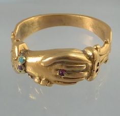 "English ca 1700 gold Fede ring, the hand ""was"" enamelled / one can still see the white enamel still between the fingers / On the ""middle finger "" a small ruby glass as a finger ring. The cuf..."