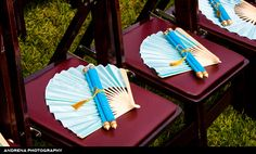 I've seen these! sometimes they give out programs at the wedding to explain the Indian ceremony so that the audience can participate with each part! I love the idea of putting it on scrolls! (It would be cool if the scrolls were removable to become dandiyas as a take home gift)
