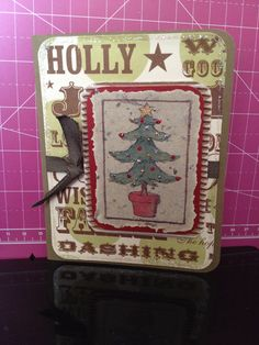 Rustic Rub-on Tree, CST 12/18/13. Card base is Stampin' Up, background paper is Making Memories Words Twinkle, ribbon is SU Always Artichoke. Also used corrugated cardboard inked with SU White Craft ink, misc textured red cardstock, and a rub-on tree from ProvoCraft First Impressions. Finished by outlining the background paper with Star Dust Stickles and using Xmas Red, Silver, and Gold Stickles with Scattered Straw Distress Stickles on the tree. For Loren.