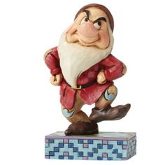Jim Shore's 7 Dwarfs collection offers a whimsical take on the lovable characters from Disney's Snow White. This colourful Grumpy has a disapproving look, but beneath that gruff exterior lies a heart of gold.