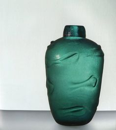CORROSI, 1936-1938 > si distinguono per la caratteristica superficie scabra dovuta all'aggressione dell'acido fluoridrico e solforico in soluzione. Il manufatto, in spesso vetro trasparente colorato, una volta raffreddato viene cosparso di segatura impregnata di acido: si ottiene così una corrosione irregolare della superficie esterna dell'oggetto, che a volte veniva iridato. Con questa tecnica Scarpa ideò un'ampia gamma di vetri dalle forme morbide, decoCarlo Scarpa | Venini 1932-1947…