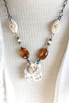 Here is a gorgeous combination of the colors cream and amber, make this understated and lovely necklace an unforgettable piece. It is so very elegant in its simplicity. The necklace is composed of three remnants of a mid 1900s necklace of celluloid and rhinestone links. They are ivory/cream colored and the rhinestones are bright. There are two oval swarovski crystal stones of amber/topaz color. Length is a bit over 20 long, but it can be clasped at any point along the chain to shor...
