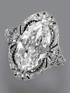 Diamond ring, circa 1915. The marquise-shaped diamond weighing 3.71 carats, in a pierced frame of conforming shape decorated with small single-cut diamonds and calibré-cut simulated sapphires, mounted in platinum. by nora
