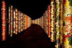 Illuminated poles decorated with Kyo-yuzen fabric.  Kimono Forest, Kyoto, Japan.