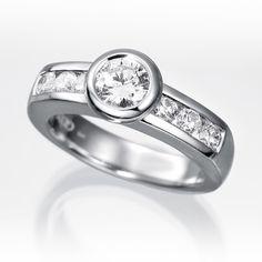 Anillo solitario de diamantes LIMA  Anillo solitario con diamante central talla brillante engastado en una montura de oro blanco de 18 kilates o platino fino de boquilla y seis diamantes talla brillante en los brazos.