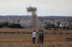 Tre uomini turchi osservano da Sanliurfa, Turchia, la cittadina di Kobane, Siria, sotto attacco degli jihadisti dello Stato Islamico. La foto mostra l'incredibile prossimità tra le milizie Isis e la Turchia (Stringer / Getty Images)