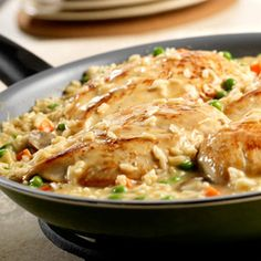 Chicken and Roasted Garlic Risotto  4-skinless, boneless chicken breast halves (about 1 pound)  1 tbsp.-butter  1 can-(10 3/4 ounces) Campbell's® Condensed Cream of Chicken Soup (Regular or 98% Fat Free)  1 can-(10 3/4 ounces) Campbell's® Condensed Cream of Mushroom with Roasted Garlic Soup  2 cups-water  2 cups-uncooked instant white rice  1 cup-frozen peas and carrots