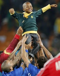 SOUTH AFRICA, SOWETO : A South African boy who invaded the pitch is carried by Brazil's players at the end of a friendly football match between South Africa and Brazil at Soccer City stadium in Soweto, outside Johannesburg, on March 5, 2014 ahead of the 2014 FIFA World Cup football tournament. Brazil won 5-0. AFP PHOTO / MARCO LONGARI