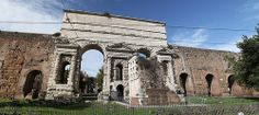 """A panoramic view of the east side of the Porta Maggiore in Rome, made up of six separate photographs. Traces of the piers that supported the Claudian aqueducts can be seen in tuff (tufa) blocks on the left and right sides of the travertine """"gate."""" It was not meant as a gate when first built (52 CE) but a monument to the entry point of the aqueducts to Rome. In the center foreground are the remains of the Tomb of Eurysaces."""