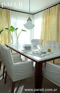 """También el comedor se beneficia con sus ventanas en """"L"""" que incorporan una luminosidad increíble. Allí, una mesa con base de lapacho macizo y tapa en mármol de Carrara ($ 5.500) y sillas de madera de guindo con apoyabrazos que se visten con fundas de <i>bull</i> blanco ($ 900 c/u) componen un cálido ambiente rematado por una lámpara de estilo <i>art decó</i> ($ 1.500, todo de <i>Mariana Pussacq</i>)."""