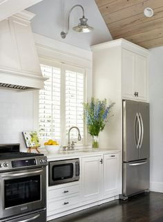 CHIC kitchen with hood cover and stainless steel appliances.
