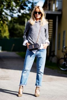 Gray sweater worn over a white collared button-down shirt, cuffed boyfriend jeans, and lace up heels