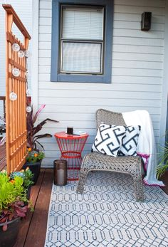 You can carve out a chill spot on your patio or balcony no matter the size of the space. A comfortable lounge chair, a plant stand turned side table, twinkling lights, and layers of plush pillows and a blanket make this a cozy retreat.