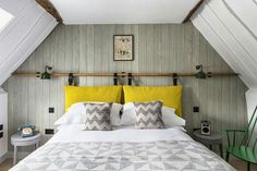 At the Old Stocks Inn in Stow-on-the-Wold, the rooms are contemporary and relaxed. This attic bedroom features original beams which look striking against the chic grey and white scheme. Be inspired to make you're own - a simple wooden pole hung with fabric cushions is an interesting and inexpensive way to mimic the look of a designer headboard.