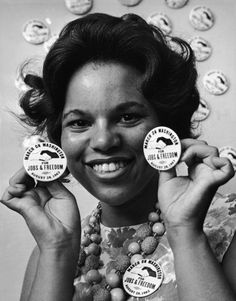 Civil rights campaigner and organizer Karen House holds up buttons for the 'March on Washington for Jobs & Freedom,' several weeks before the August 28, 1963 event. The buttons, which depcit a black hand and a white hand clasped in solidarity, were supplied by the NAACP. Photo by Arnold Sachs/Getty Images.