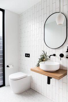 Espejo ovalado de borde metálico negro, ideal para crear un genial contraste con el luminoso blanco de las paredes y los sanitarios. #tendencias2020 #tendenciasdecoracion #bañosmodernos #espejosparabaños