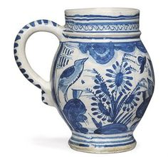 A SOUTHWARK DELFT DATED BLUE AND WHITE MUG  1630, PROBABLY CHRISTIAN WILHELM, PICKLEHERRING QUAY  Of barrel shape with short cylindrical neck, the loop handle with blue-dash ornament, painted with 'birds-on-rocks' flanked by flowering plants beneath a band of stylised drapery, flanked by two vertical panels and the date 1630 beneath the handle, the neck with a band of cable-ornament between concentric blue lines and with three concentric blue lines to the foot  4 7/8 in. (12.5 cm.) high