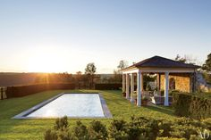 A columned cabana is situated alongside the discreet swimming pool of an elegant New York farmhouse.