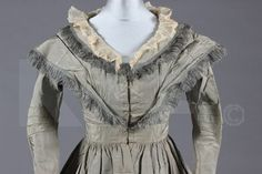 Pink/Gray silk changeable taffeta gown, late 1830s - early 1840s. Kerry Taylor Auctions, Lot Number: 374. Item Description: A changeable pink/ grey silk taffeta pelisse robe, late 1830s -early 1840s, the double collar edged with silk fringes, hook and eye fastening to front, bust 86cm, 30in. Original net or lace collar/tucker still attached.