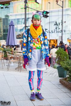 Kanata has partially shaved hair with green bangs and colourful pompoms and hair pins. His face mask features a strawberry print. His Hello Kitty jacket is from Kinji, worn over a M&M print t-shirt. He is also wearing high waist sheer shorts over colorful leggings, a yellow muffler, knitted gloves, earrings, a yellow backpack and Reebok sneakers. He told us his accessories are Candy Stripper.