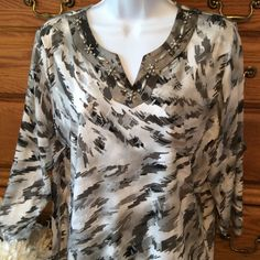 "Alfred Dunner Gray Embellished Tunic Colors of gray, silver and some black.  Gray colored embellishments around the neckline in the front only.  92% polyester and 8 % spandex.  Excellent condition.  Really doesn't wrinkle. . Approximately 25"" in length and when laid flat measuring armpit to armpit it is 21"" across.  Petite Medium. Alfred Dunner Tops Tunics"