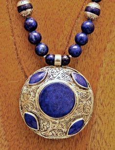 This is an all-Asian piece of jewelry - Afghani Turquoise, Kazakh silver and artisan work, and Nepalese Silver-capped Lapis. So blue!    The pendant is a handmade puffed and etched circle pendant bezel set with a large round and 4 bicone Lapis Lazuli beads. The Lapis is beautifully polished as is the silver