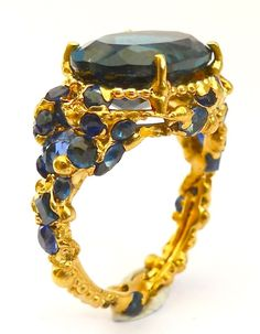 Polly Wales. Bismarck Ring. Oval London blue topaz in an 18ct yellow gold setting embedded with antique blue sapphires