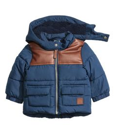 Dark blue. Padded jacket with a detachable, pile-lined hood. Zip at front, front…