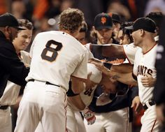 San Francisco Giants' Buster Posey, center right, bent over, is mobbed by teammates after hitting the game-winning home run off Colorado Rockies' Juan Nicasio in the ninth inning of a baseball game Wednesday, Aug. 27, 2014, in San Francisco. The Giants won 4-2. (AP Photo/Ben Margot)