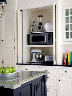 A three-level cabinet has spaces just the right height for a mixer, microwave oven, and other small appliances. Retracting doors clear the countertop when appliances are in use./