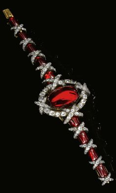 An exceptional garnet and diamond bracelet, circa 1860. The centre set with an oval cabochon garnet within a border of circular-, single-cut and rose diamonds, to a tapered bracelet of polished garnets highlighted with a diamond set ribbon motif, length approximately 210mm, Russian marks and work-master's mark, accompanied by later fitted case, Rath.
