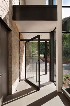 Dramatic stone and glass home in Aspen surrounded by forestLike the large glass pivot door and concrete floor Contemporary Mountain Home-Charles Cunniffe Kindesign Modern Front Door Designsfarebnost- 2 druhy dreva!Interior Design by Contemporary Front Doors, Modern Front Door, Front Door Design, Modern Entryway, Entry Doors With Glass, Glass Front Door, Exterior Doors With Glass, Glass Doors, Front Door Entrance