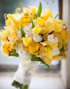 White hydrangeas add texture to a vivid bouquet of yellow orchids, tulips, ranunculus and craspedia.