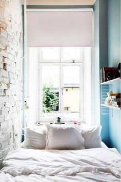 Very small bedroom with exposed brick, white bedding, and side shelving.