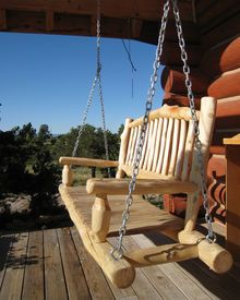 stock photo of log cabins - Wooden swing on the porch of a log cabin in the country - JPG