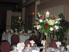 Love the pillar candle with hydrangeas, larkspur, roses etc on a classic brass stand