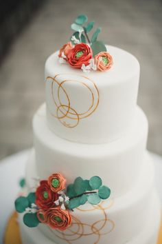 Gold rings and paper flowers add whimsy and elegance to this fondant wedding cake. {Zingerman's Bakehouse}