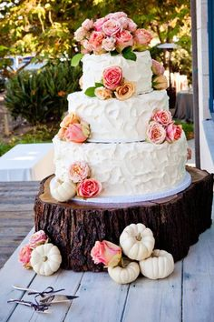A rustic vintage wedding cake with fresh roses and sweet mini white pumpkins.