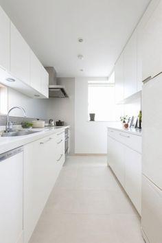ベージュの床タイルの色合いが、白×グレーのキッチンをやさしい印象に仕上げています。