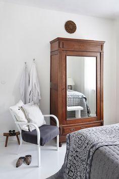 Ranskalaisessa antiikki-kaapissa säilytetään juhla-vaatteita ja kenkiä. Valkoinen nojatuoli on kirppislöytö, jonka Niina maalasi valkoiseksi ja päällysti istuinosan Lauritzonin kankaalla.