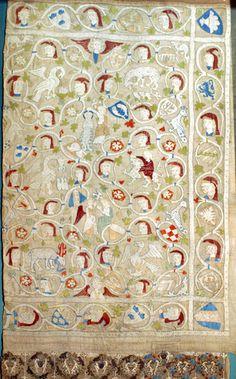 DI 76 (Lüneburger Klöster) Kloster Isenhagen 2./3. V. 14. Jh.    Signatur: DI 76, Nr. 22    Behang.1) Leinen mit Seidenstickerei. Der Behang ist im Museum ausgestellt. Der linke Teil nicht erhalten. Auf den Rahmenborten im Wechsel Köpfe und Wappenschilde, auf einer unten angesetzten Borte kleinere Wappenschilde mit je zwei Tieren als Wappenhalter.2) Im Innenfeld von Köpfen, Wappenschilden und Blumen im Wechsel umgebene Darstellungen: Pelikan, Löwe mit seinen Jungen, ein seine Jungen mit…