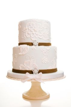 Pretty white on white flower cut outs and brown ribbon trim on a two layer wedding cake.