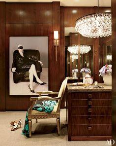 The dressing room in a Florida home decorated by Furze Bard + Assoc. features an Ochre chandelier, a Boo Ritson photograph, and a Porta Romana sconce.