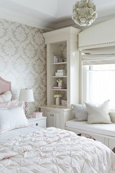 Bedroom window seat flanked by bookshelves. A built-in window seat with storage stands under a picture window dressed in a white curved cornice box finished with silver nailhead trim flanked by tall built-in bookcases Tara Fingold Interiors