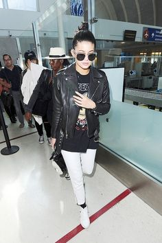 Kylie Jenner wears a Yeezus graphic t-shirt, moto jacket, cropped white pants, black socks, and high-top sneakers