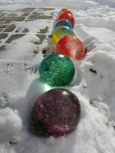 Fill balloons with water and food coloring. Set them outside to freeze. Once frozen cut away the balloon. Could be marbles or giant Christmas ornaments.