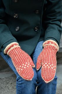 With long welted cuffs and a stranded colourwork pattern, these luxurious mittens are toasty warm and have a vintage feel. Clever construction allows the contrast colour band to run up and around each thumb, finished off tidily by grafting the last few stitches at the tip of each hand.