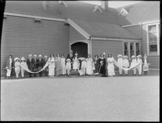 Group in fancy dress, showing a group of unidentified women and children dressed as a royal family and attendants, including pageboys and a man dressed as a judge, outside a wooden [hall?] building, possibly Christchurch district